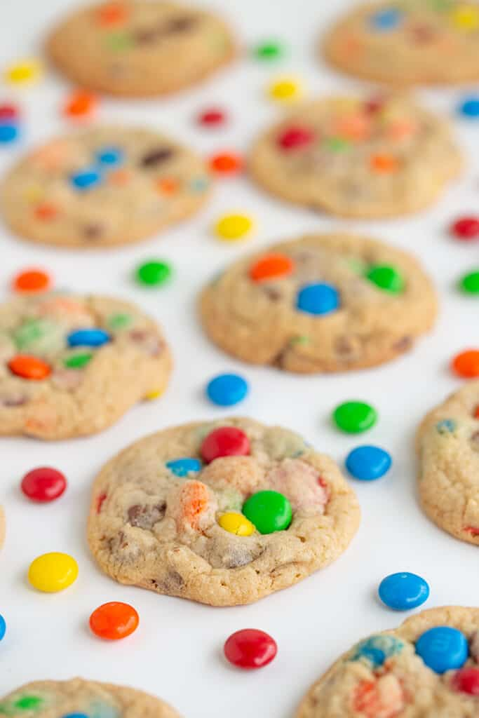 cookies on a white surface with M&M candies around the cookies