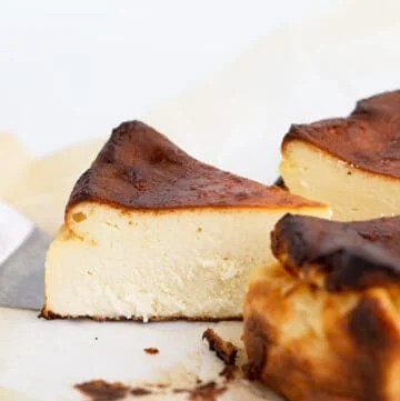 Slice of cheesecake being served up from the whole cheesecake