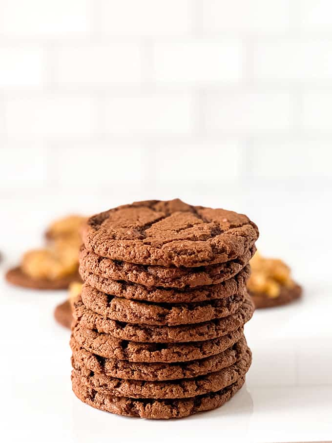 stack of chocolate cookies on a white surface with other cookies with topping behind the stack