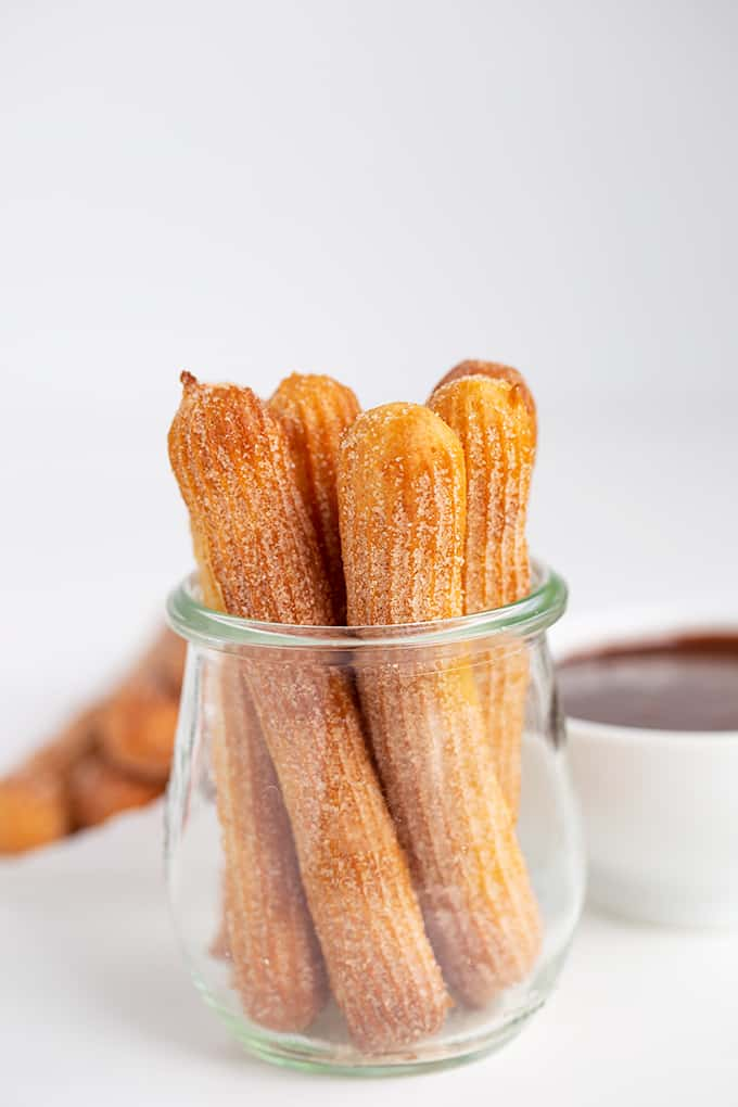 small glass jar with churros in it with dipping sauce in a white bowl behind it