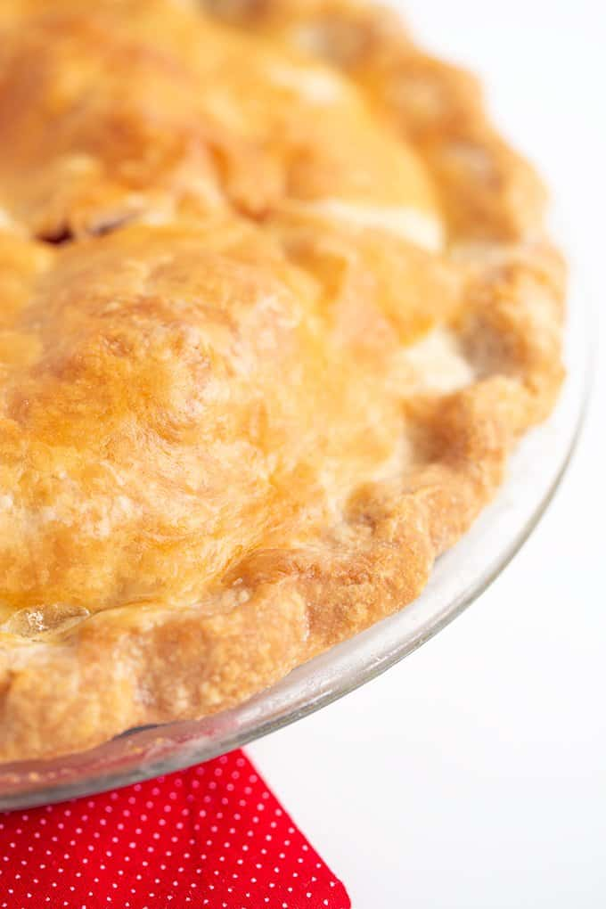 picture focusing on the edge of the crust of a pie on a white surface with a red fabric