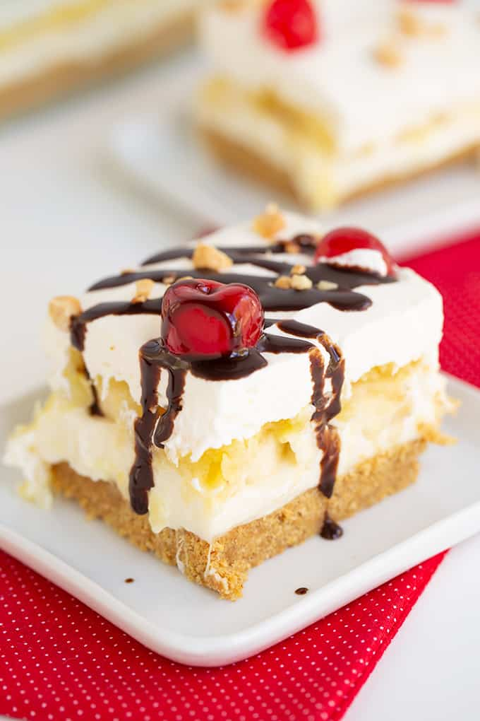 slice of no bake banana split cake on a small white plate with a red fabric under it and chocolate syrup dripping down the dessert