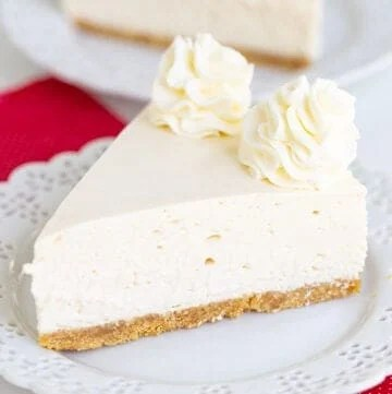 cheesecake on a small white plate with a red linen under the plate