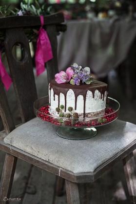 rustikaler Stuhl mit Blumengirlande in violett und Drip Cake, Herbstdekoration