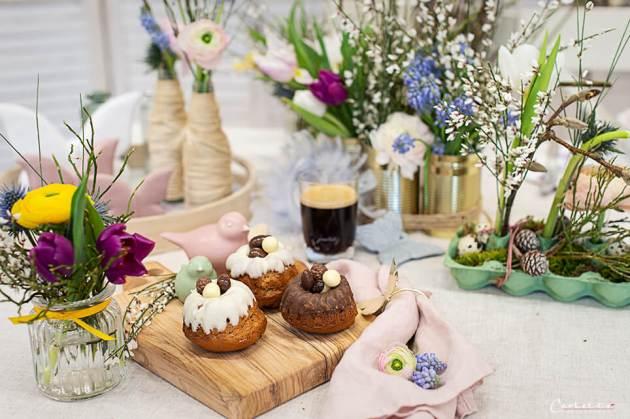 Mini Kaffee Gugelhupf mit weißer und brauner Schokoglasur und kleinen Dragee-Eiern verziert. Auf einem Frühlingstisch angerichtet.