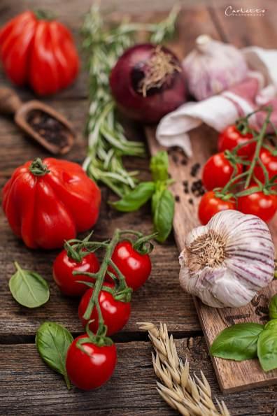 Tomaten an der Rispe, Knoblauch und Basilikum auf einem Holzbrett
