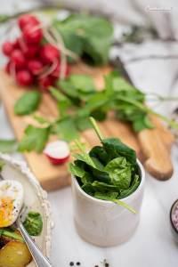 Frühlings Salat - Frischer Spinat mit knusprigen Kartoffelspalten und halbieren festgekochten Eiern