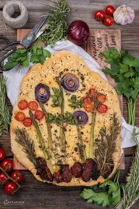 Italienisches Fladenbrot mit Gemüse in Form von Blumen belegt