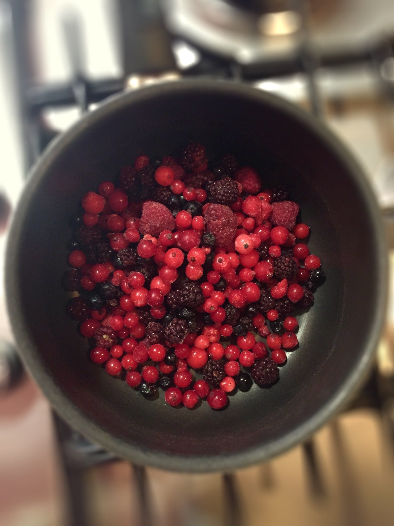 cooking berries sauce for a dessert in a glass