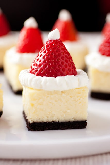 Santa Hat Cheesecake Bites - cheesecake squares layered with oreo crust, white chocolate cheesecake filling and topped with strawberries, whipped cream