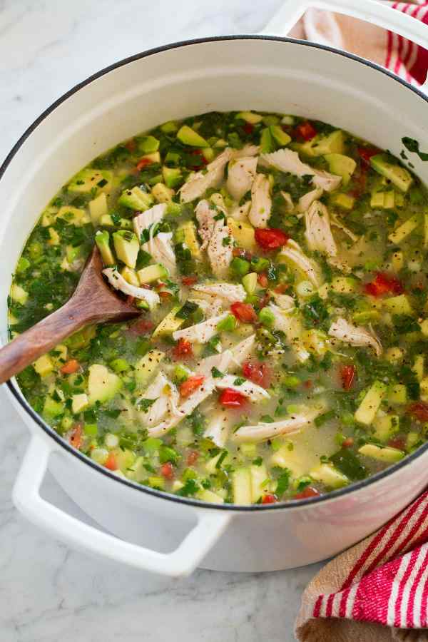 White pot filled with chicken soup with avocado and tomatoes.