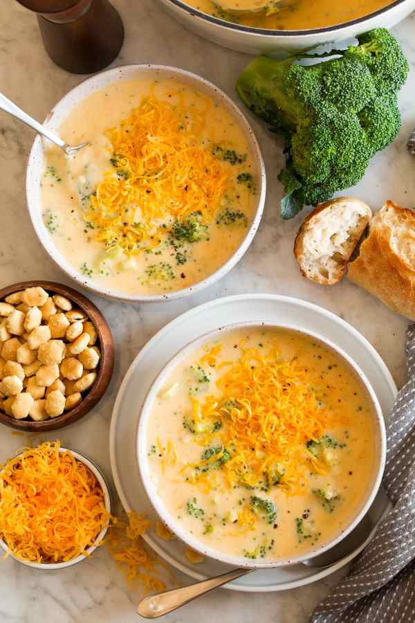 Overhead image of two servings of broccoli cheese soup in serving bowls. Crackers, broccoli, bread, and cheese are shown to one side.