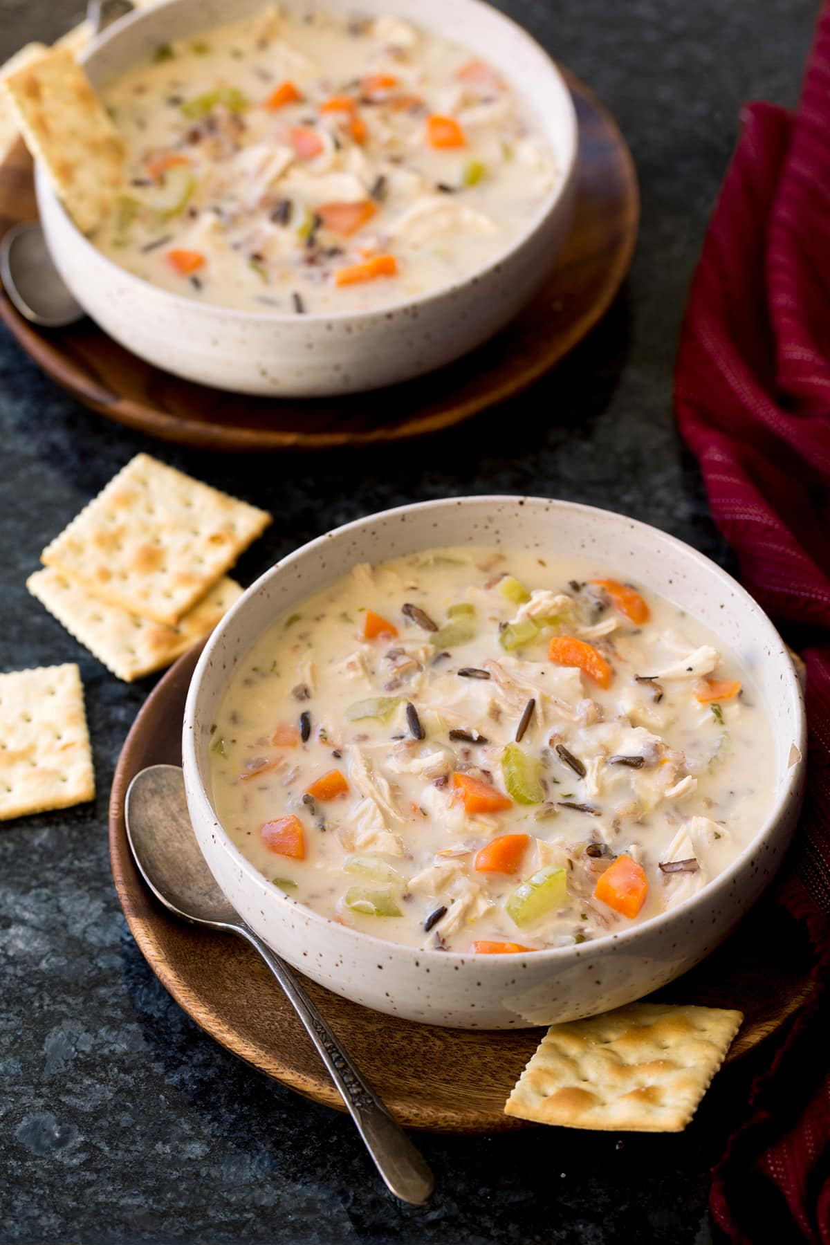 Two servings of chicken and wild rice soup in serving bowls.