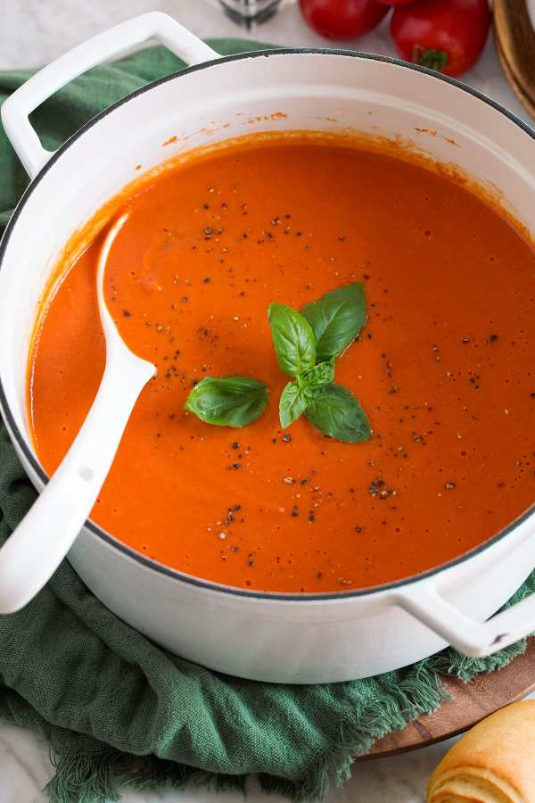 Image of the white saucepan filled with tomato soup that is garnished with basil and pepper.