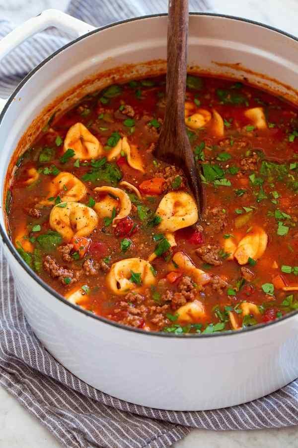 White pot full of tortellini soup.