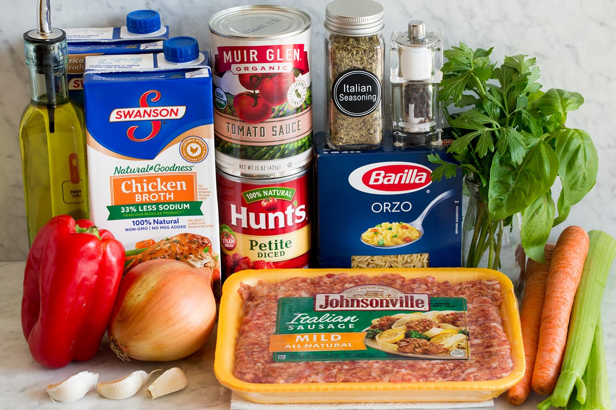 Image of the ingredients used to make Italian sausage and orzo soup. Contains mild Italian sausage, orzo, carrots, celery, basil, parsley, Italian spices, salt and pepper, tomato sauce, tomato cubes, chicken broth, yellow onion, paprika, olive oil and garlic.