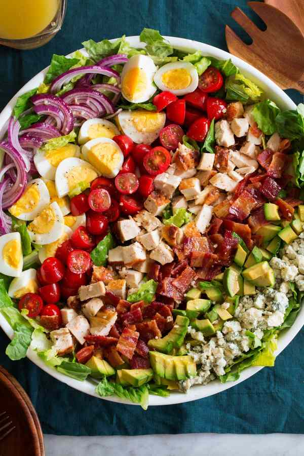 Overhead photo of cobb salad with blue cheese, avocado, bacon, chicken, tomatoes, hard boiled eggs, red onion and romaine lettuce in a large white bowl.