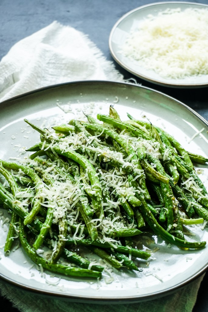 Side shot of green beans piled on a plate with grated parmesan on top