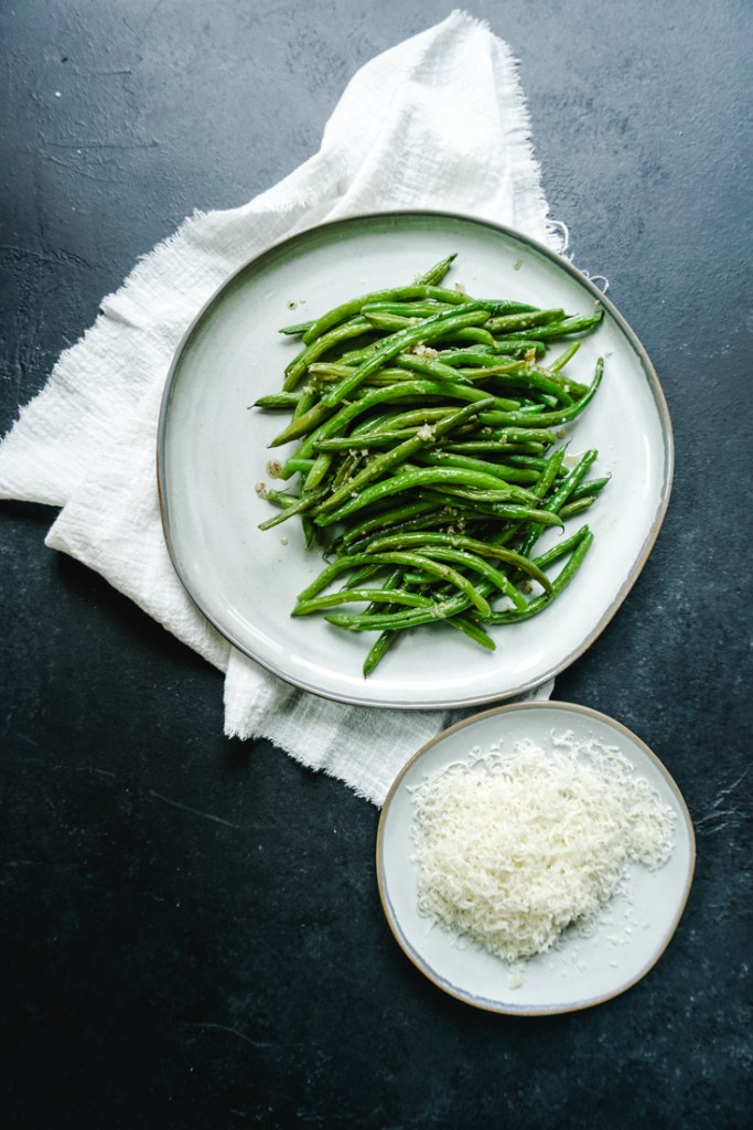 Baked green beans piled up on a plate with a white napkin under it and a smaller plate of grated parmesan next to it