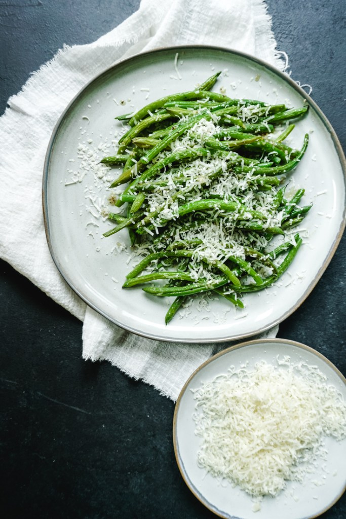 Green beans piled on a plate with grated parmesan on top and a plate of grated parmesan on the side