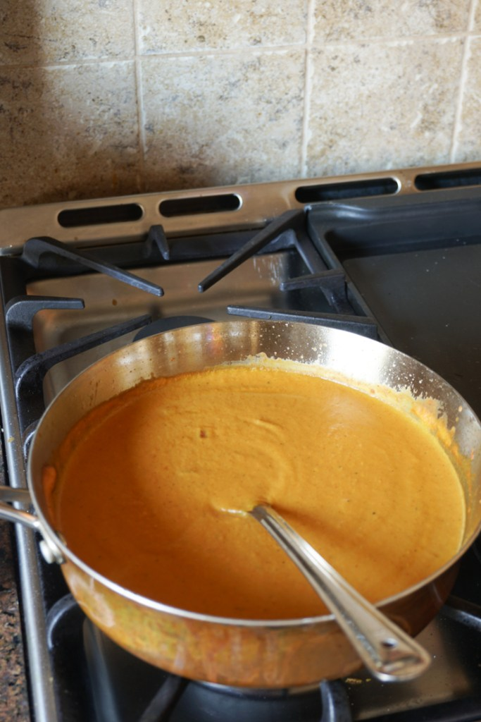 Stainless steel sauce pan on stove with sauce in it