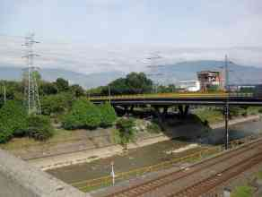 river, train tracks, bridge with Medellin hills in background