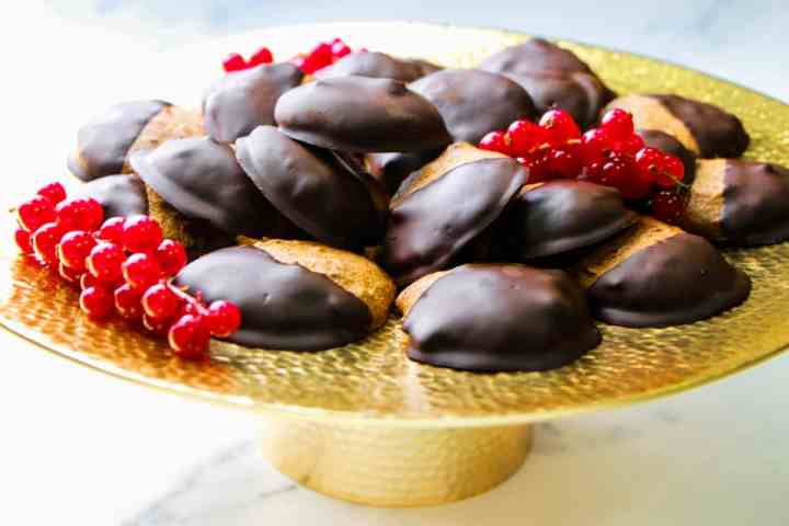 Photo of dark chocolate dipped almond cookies piled on a brass cake stand with redcurrants, all on a marble surface.