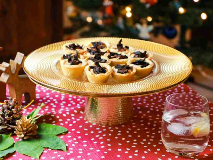 a brass cake stand with mushroom bacon tartlets in a christmassy scene with a drink to the front right and christmas decorations to front left and a christmas tree in the background.