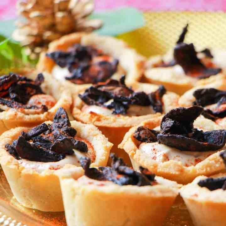 Close-up photo of a plate of mushroom bacon and black garlic cashew cream tartlets