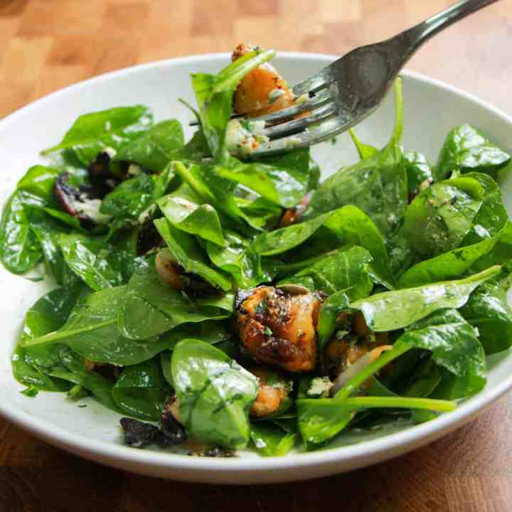 bowl of spinach, squash and mushroom bacon salad mixed with dressing and a fork digging in.