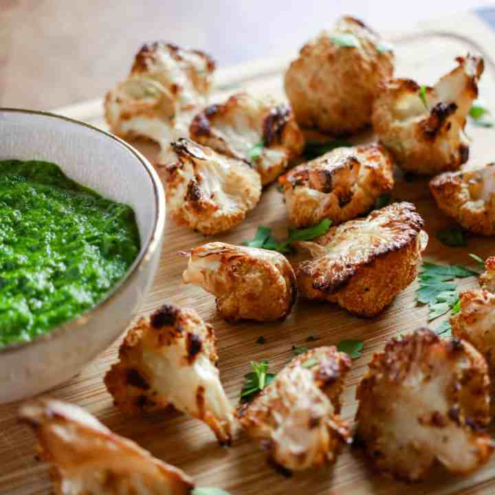 roasted cauliflower pieces on a wooden chopping board with a bowl of chimmichurri sauce on the side.