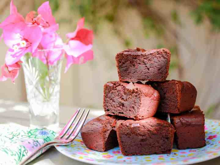 a pile of vegan and gluten-free chocolate beetroot brownies on a flowery plate with a fork and a pretty vase with pink flowers in the background.