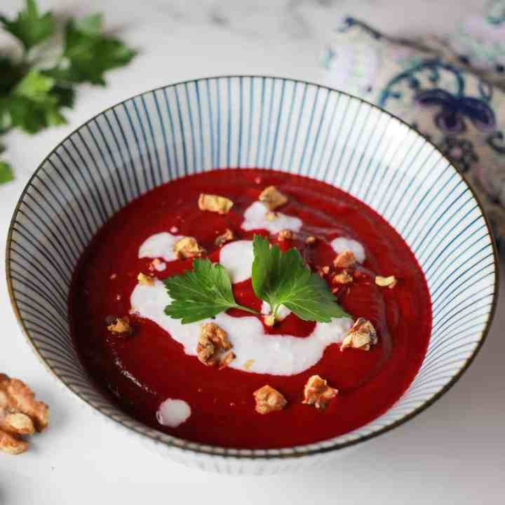 photo of a blue and white striped bowl with deep pink beetroot and walnut soup and dotted with coconut cream, walnut pieces and a sprig of parsley.