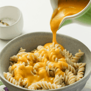 Pinterest graphic for Healthy Vegan Cheese Sauce with green jug pouring source over a bowl of twirly pasta, all on a white background.