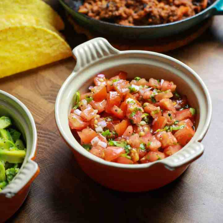 Photo of a dish of fresh salsa on a wooden background with tacos behind and a pan of vegan taco meat behind and a bowl of guacamole just on the edge to the left.