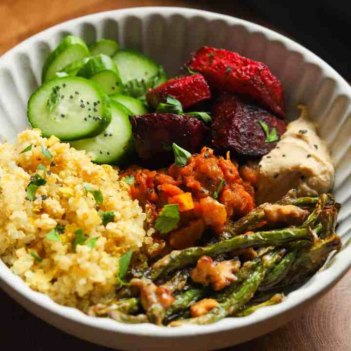 Photo of a white bowl with some roasted beetroot alongside some quinoa, chopped cucumber, roasted green beans with walnuts and some hummus and Mirza ghasemi (aubergine and tomato dip).