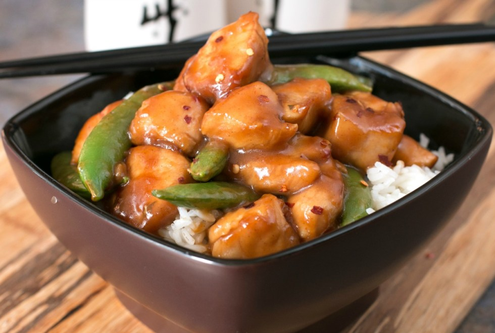 A black bowl filled with orange chicken recipe with snap peas and rice