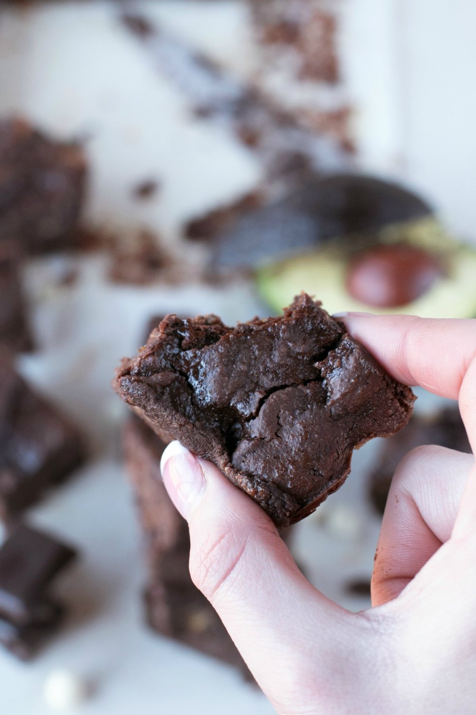 A hand holding a single avocado brownie with a bite out above other brownies in background