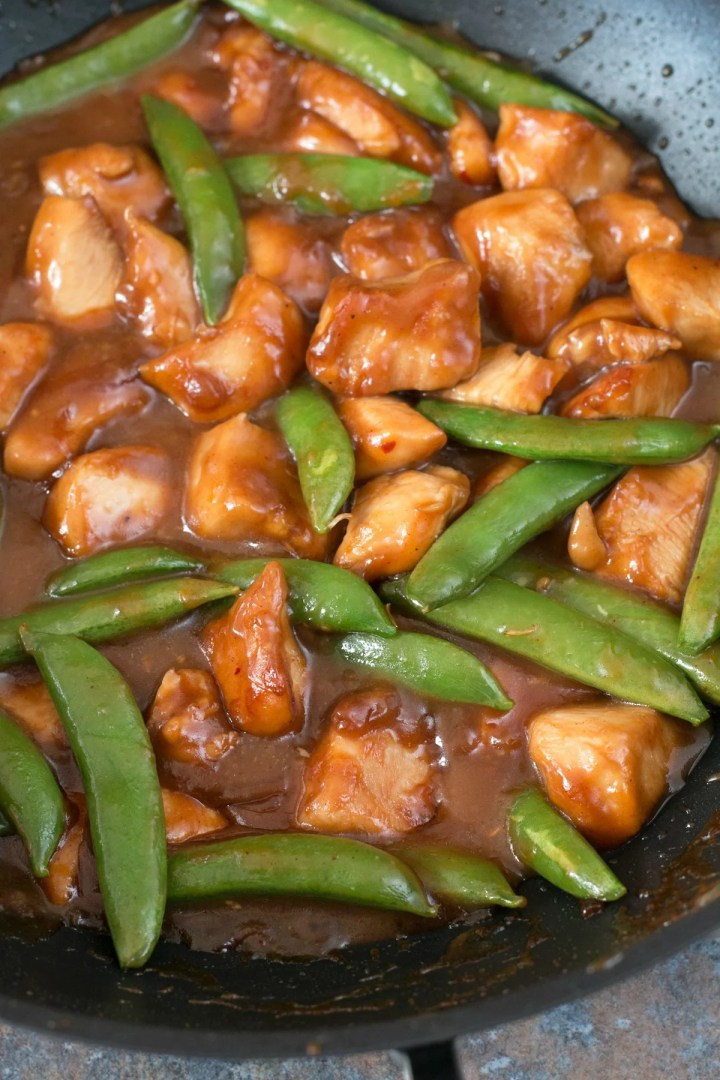 Orange chicken with pea pods in a wok being stir fried