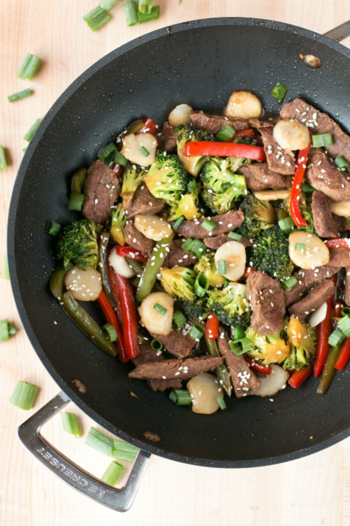 A large wok filled with beef stir fry and vegetables that is sitting on a wooden surface