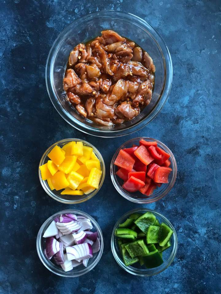 Ingredients for chicken shish kabobs - marinated chicken, yellow, red, and green bell pepper and red onions
