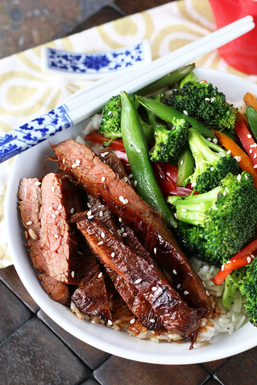 Image of soy marinated flank steak stir-fry with white and blue chopsticks on the bowl and a white and brown napkin in the back.