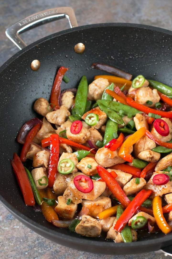 Sweet and Spicy Chicken Stir Fry in a dark non-stick skillet.