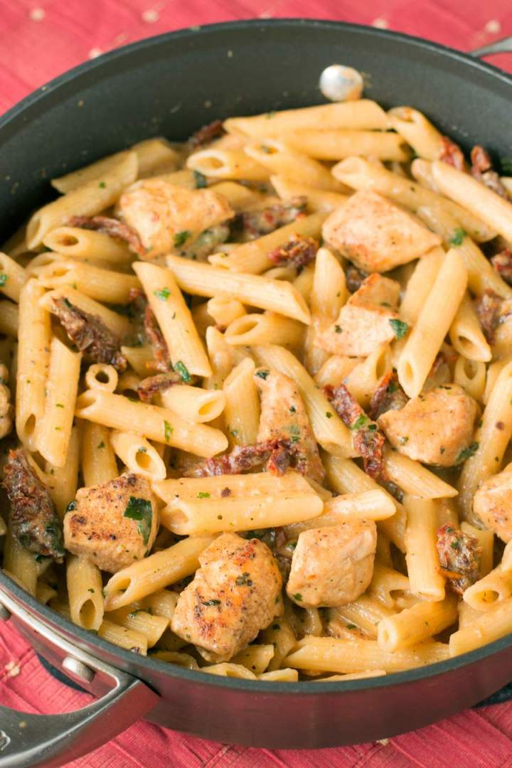 Sun-dried tomato penne pasta with chicken in a skillet on a red tablecloth.