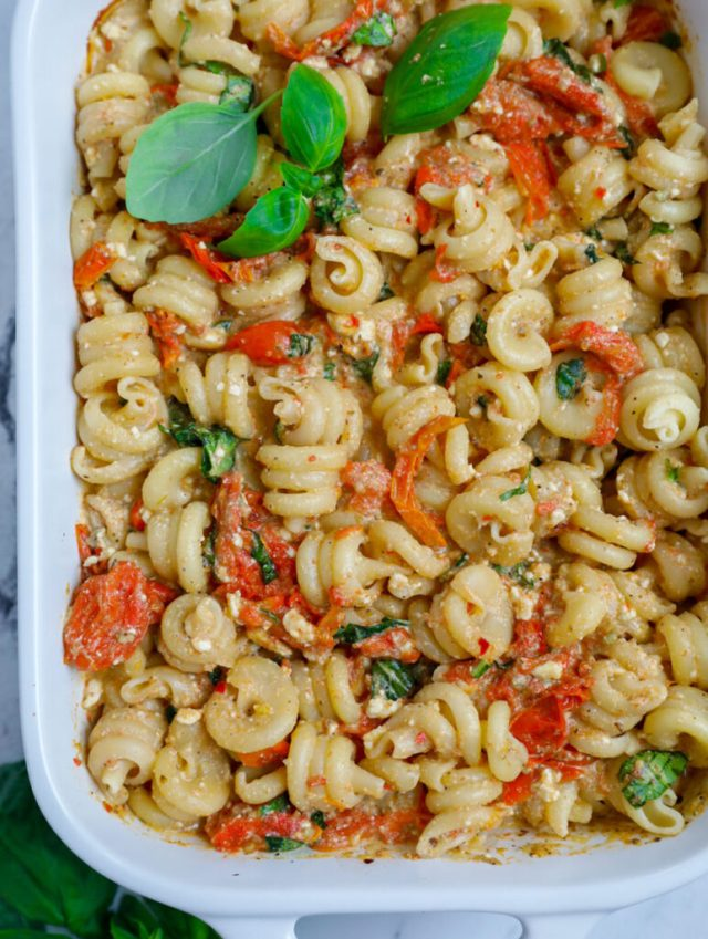 Baked cheese pasta in a casserole dish with basil garnish.