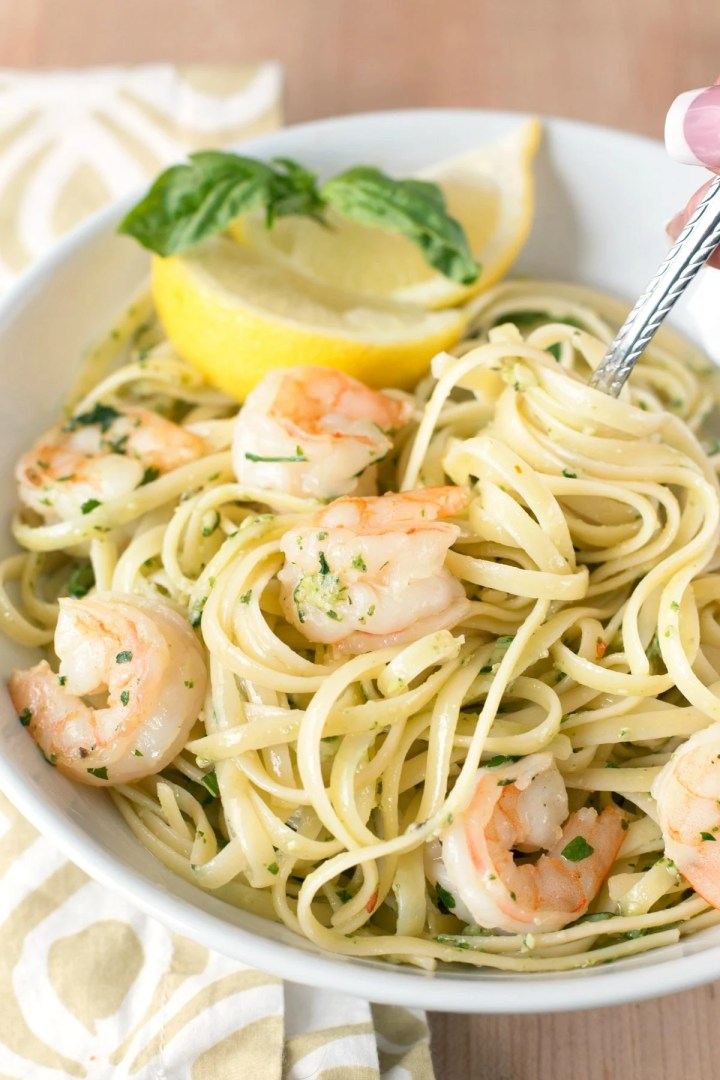 Overhead picture of a large white bowl of pasta with pesto shrimp scampi and lemon slices