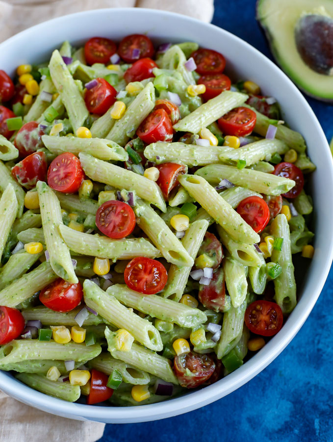 A large white bowl of creamy avocado pasta salad on a cream colored dish towel with an avocado half at the top on a blue counter.