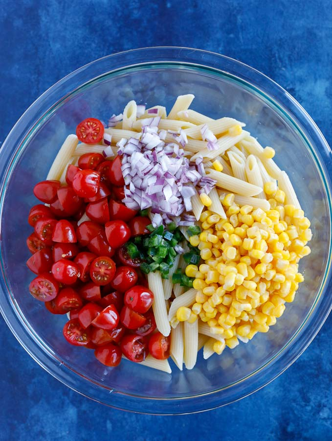 Glass bowl with penne pasta, corn, grape tomatoes, dicd purple onion, and jalapeños on a blue counter.