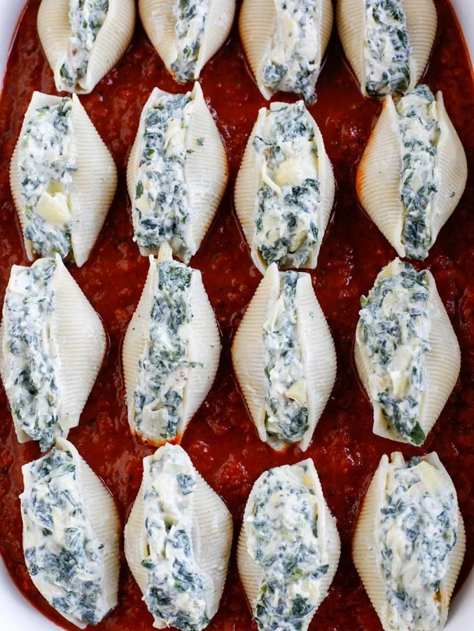 Spinach artichoke stuffed shells lined up in a baking dish.
