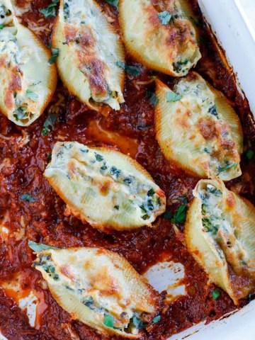 A baking dish with spinach artichoke stuffed shells in tomato basil marinara sauce.